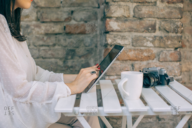 Woman using tablet at outdoor cafe table