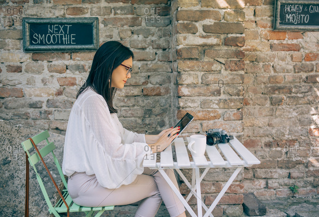 Woman using tablet at cafe table next to brick wall