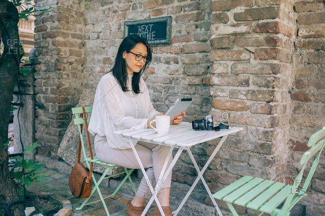 Woman using tablet in coffee shop garden