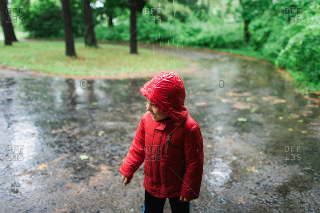 Boy in red coat playing in rain