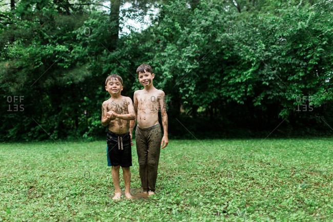 Two mud covered boys in backyard