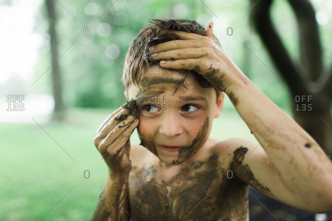 Young boy painting himself with mud
