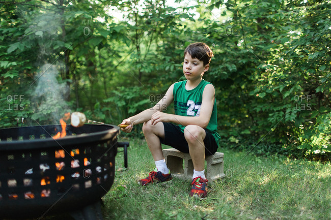 Boy toasting marshmallow at campfire