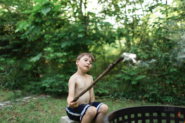 Boy playing with stick at campfire