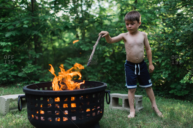 Boy with stick at campfire