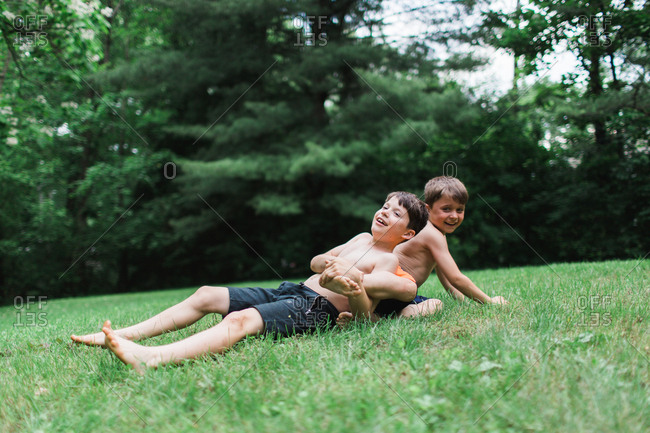 Two brothers wrestling on lawn