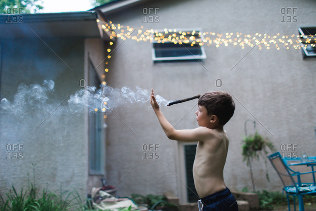 Boy experimenting with smoke coming from a stick
