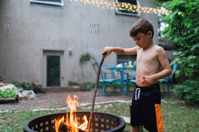 Shirtless boy poking at campfire with stick