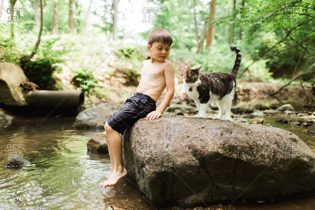 Boy sitting on rock in stream with cat