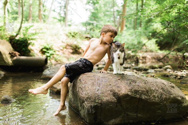 Boy with his cat on rock in stream