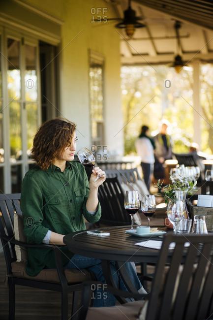 Woman sitting on a restaurant patio drinking wine