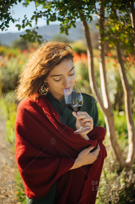 Woman standing outdoors sniffing a glass of red wine