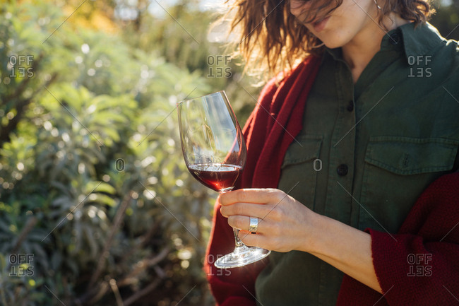 Woman standing outside swirling a glass of red wine