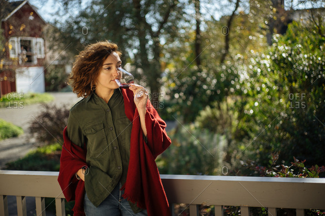 Woman standing near a barn sipping a glass of wine