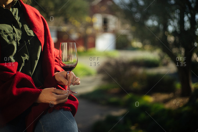Hands of a woman holding a glass of wine near a barn