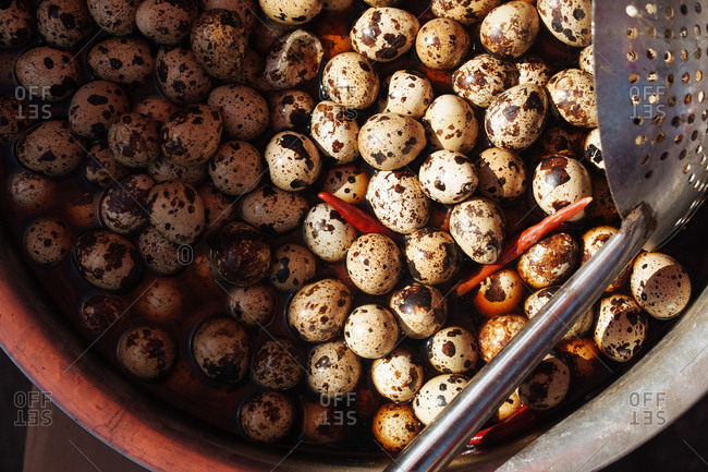 Brown speckled eggs in a large cooking pot