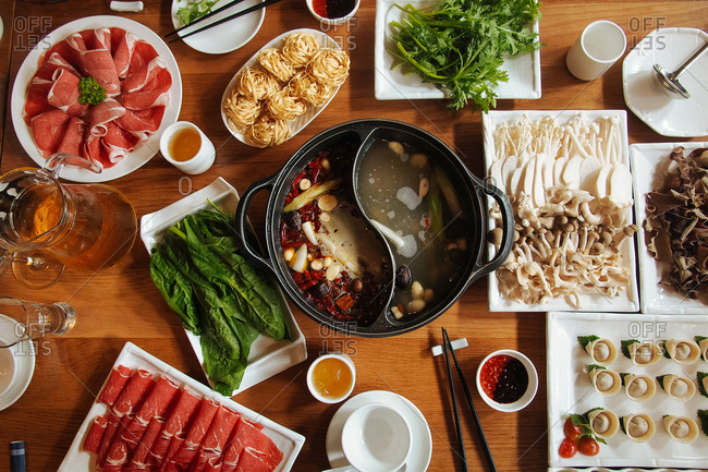 Meat, herbs, noodles and other ingredients for a dish on a wooden surface