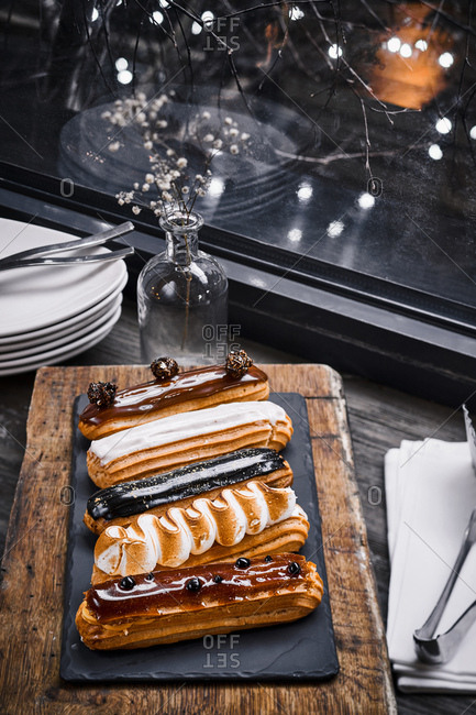 Variety of eclairs served on a slate slab on a table