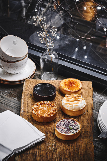 Variety of sweet tartlets on a rustic wooden board