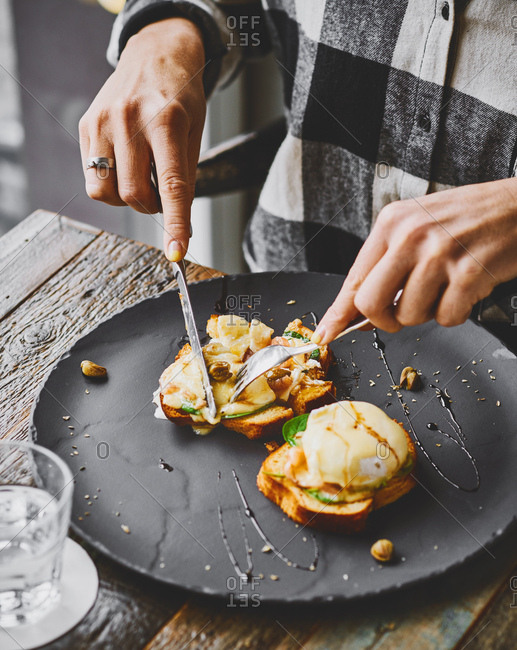 Person eating eggs benedict at a cafe table