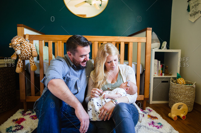 Mother and father admiring newborn baby in nursery room