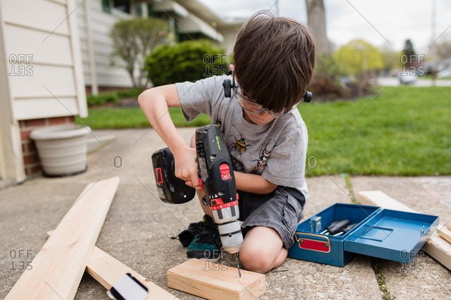 Boy drilling into block of wood