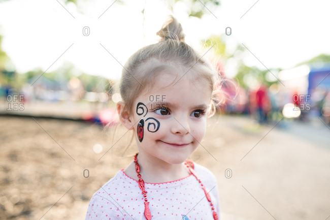 Little girl with ladybug painted on her face