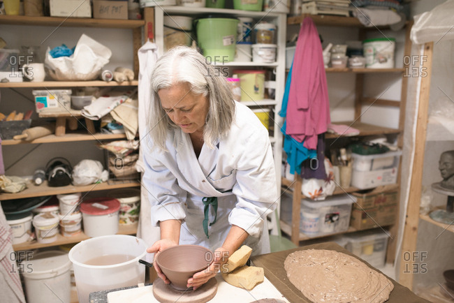 Woman making clay bowl on a pottery wheel