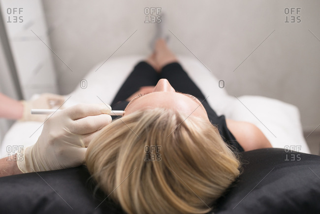Doctor marking woman's face before an anti-wrinkle injection