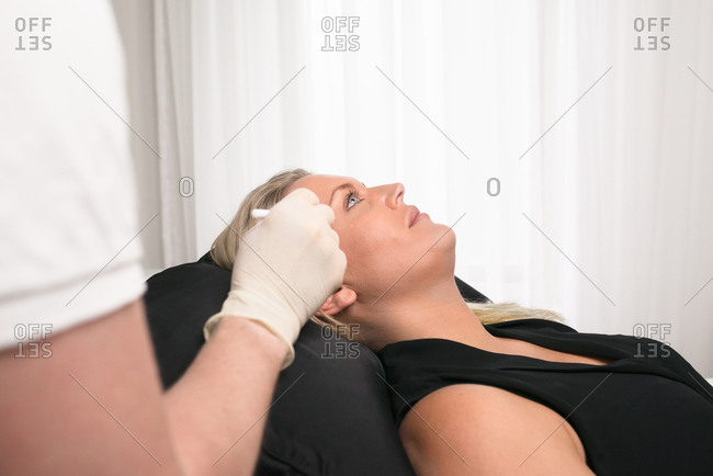 Doctor preparing woman's face before an anti-wrinkle injection