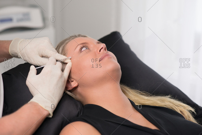 Doctor preparing to inject woman with an anti-wrinkle medicine