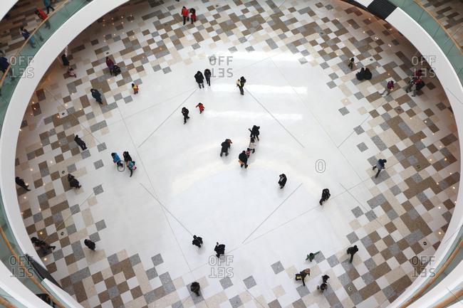 Beijing, China - December 27, 2014: Shoppers walk across the mall lobby at Wanda Plaza