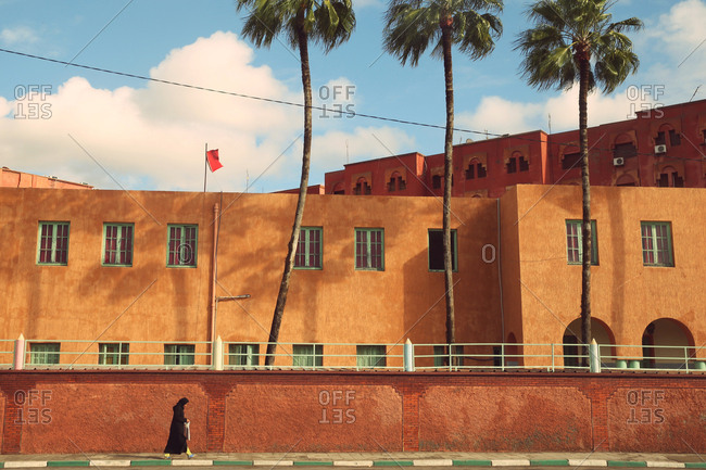 Marrakesh, Morocco - December 14, 2014: A woman walks past a fortified wall