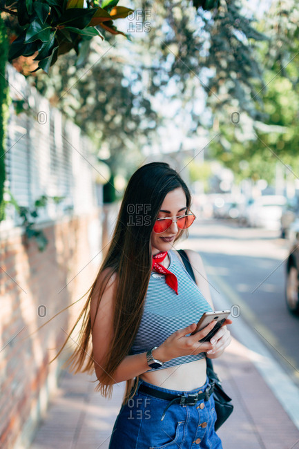 Young woman with long dark brown hair using smartphone