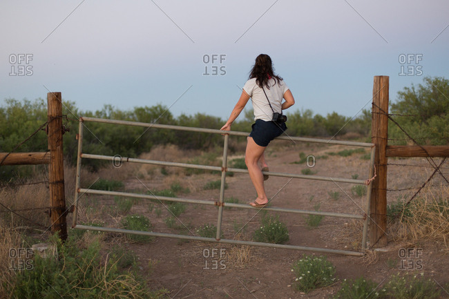 Woman with camera climbing fence