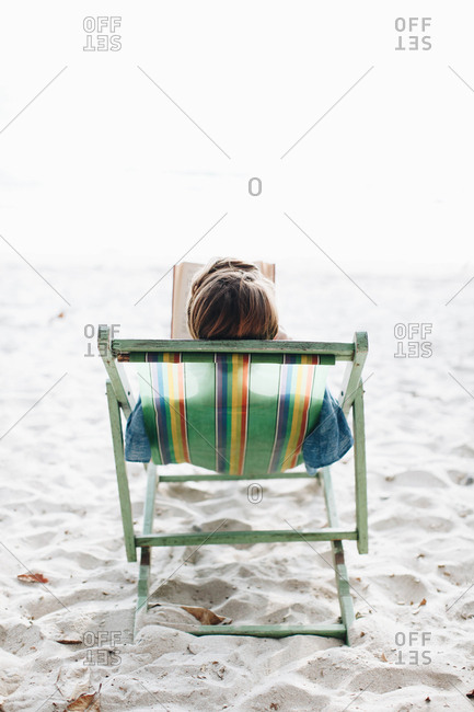 Young woman relaxes on the beach in a lounge chair while reading a book