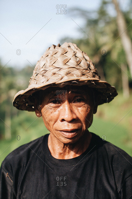 Ubud, Bali  - April 14, 2016: Portrait of a local Indonesian man wearing a straw hat on a rice terrace in Bali
