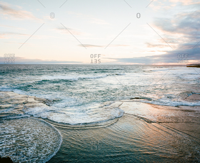 Gentle waves on beach in low light