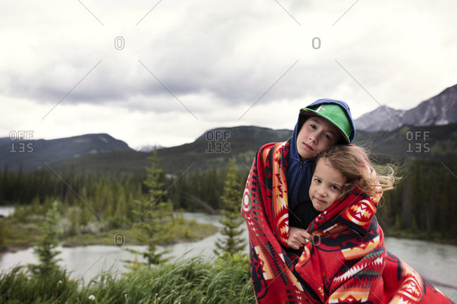 Kids under blanket in mountain setting