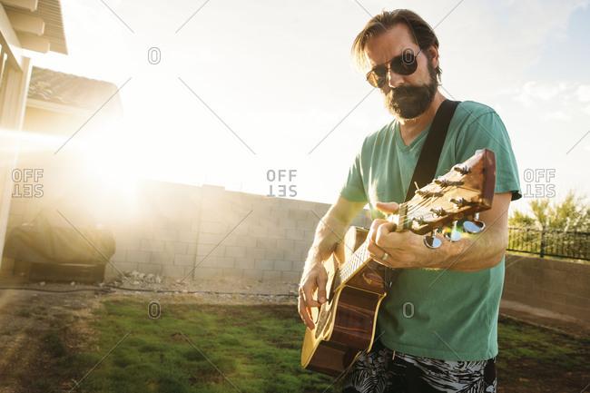 Man playing an acoustic guitar in backyard