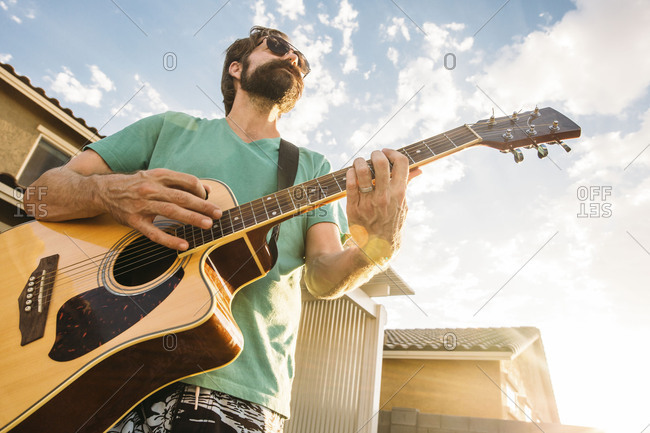 Man playing an acoustic guitar outside