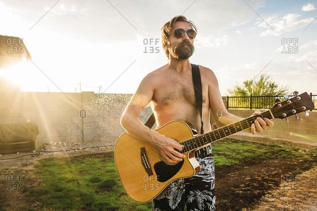 Shirtless man with beard playing an acoustic guitar in backyard