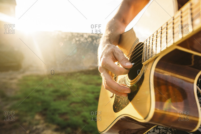 Close-up of a man picking the strings of an acoustic guitar