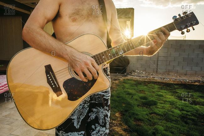 Shirtless man playing an acoustic guitar in backyard