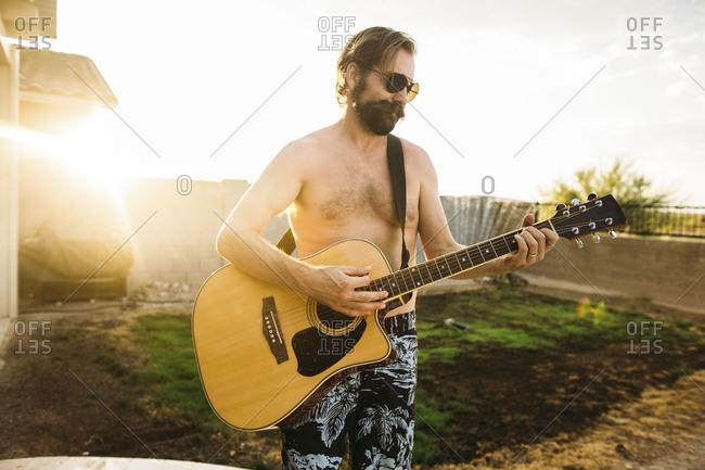 Shirtless man wearing sunglasses playing an acoustic guitar in backyard