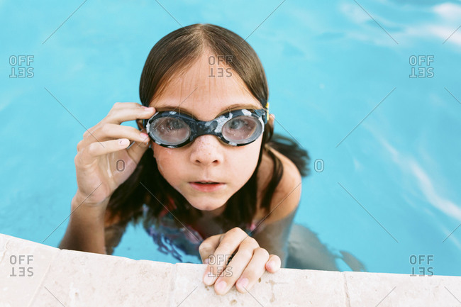 Portrait of a girl wearing goggles at edge of swimming pool