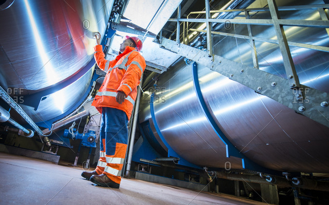 Yorkshire, England, UK - October 29, 2012: Man touching industrial pipe