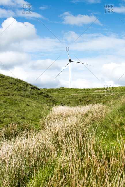 A wind turbine in hilly setting