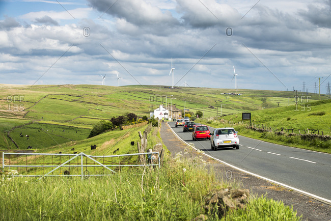 Yorkshire, England, UK - June 3, 2014: Cars driving through wind farm