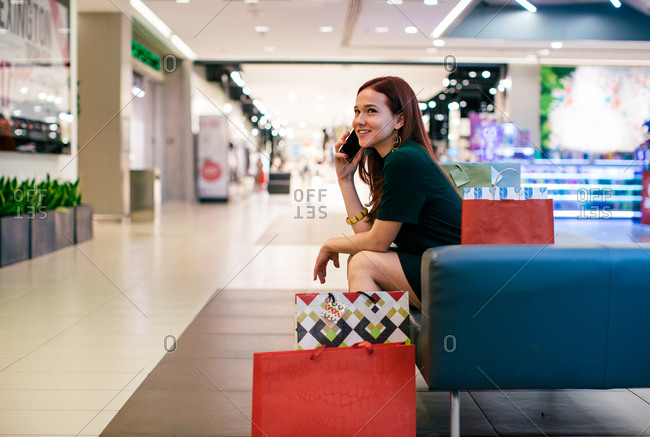 Young woman talking on her cellphone in a mall